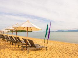 Sonnenschirme und Sonnenliegen am tropischen Strand