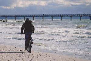 Radfahrer in dunkler Kleidung reitet auf einem Strand gegenüber Pier mit bewölktem blauem Himmel in Zelenogradsk, Russland foto