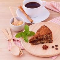 dunkler Schokoladenkuchen mit Tasse Kaffee auf hölzernem Hintergrund foto