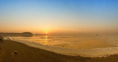 Menschen an einem Strand mit buntem Sonnenuntergang foto