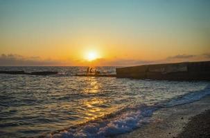 silhouettierte Leute, die am Strand bei Sonnenuntergang in Sotschi, Russland schwimmen foto