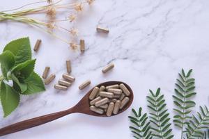 Kräutermedizin in Kapseln auf Holzlöffel mit natürlichem grünem Blatt auf weißem Marmor foto