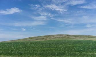 Landschaft mit Feldern und Hügeln und bewölktem blauem Himmel