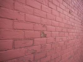 rote Backsteinmauer mit dem Abblättern der Farbe