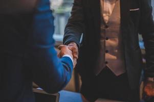 zwei Männer in Anzügen, die sich die Hände schütteln foto