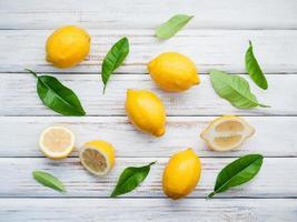 frische Zitronen und Zitronenblätter auf rustikalem hölzernem Hintergrund foto