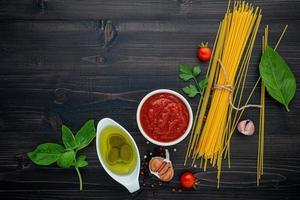 Spaghetti-Zutaten auf dunklem Holz foto