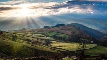 Luftaufnahme der Landschaft von Hügeln und Bäumen mit niedriger Sonne in einem bewölkten Himmel foto