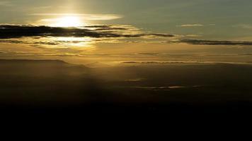 bunter bewölkter Sonnenaufgang mit Blick auf dunkles Tal