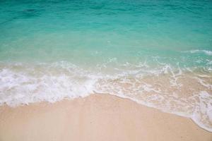 schaumige Wellen und blaues Wasser am Strand foto