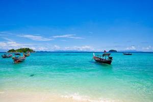 bunte Boote im blauen Wasser mit Strand und bewölktem blauem Himmel auf koh lipe Insel in Thailand foto