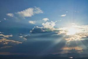Sonnenstrahlen im bewölkten blauen Himmel foto