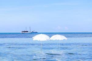 weißer Regenschirm am tropischen Sommerstrand mit Boot foto