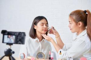 Frau zeigt Make-up-Tutorial auf Live-Video foto