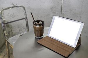 Handy arbeitet in einem Café mit Tablett mit leerem Bildschirm foto