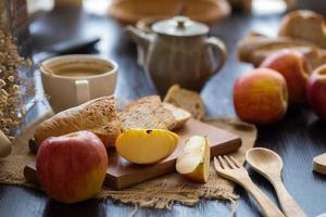 ganze und geschnittene Äpfel mit geschnittenem Baguette auf Holzbrett mit Holzutensilien, Kaffeetasse und Kaffeekanne in einem Restaurant foto