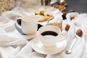 Tasse Kaffee, Untertasse und Sahneserver neben Gebäck auf zerknitterter Tischdecke foto