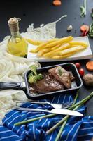 Gegrilltes Steak und Brokkoli in einer Pfanne mit Pommes Frites foto