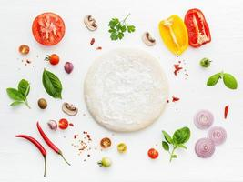 Pizzateig und Zutaten auf Weiß