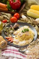 Pasta Carbonara mit Speck und Parmesan, Salat und geschnittenen Tomaten auf einem schwarzen Teller