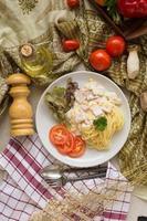 Pasta Carbonara mit Speck und Parmesan, Salat und geschnittenen Tomaten auf einem weißen Teller