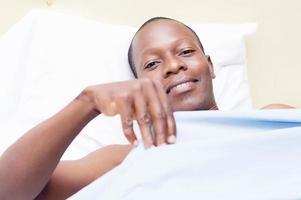 schwarzer Mann, der lächelnd in einem Bett liegt