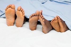 die Füße einer Familie unter der Bettdecke foto