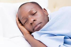 junger Mann, der im Bett schläft foto