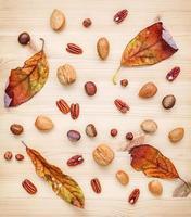 getrocknete Blätter und Nüsse auf Holz foto