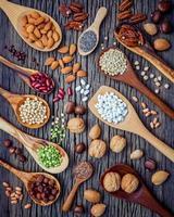 verschiedene Hülsenfrüchte und Nüsse auf dunklem Holz foto