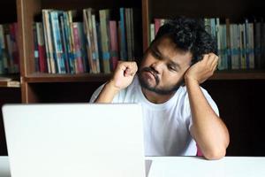 Der Mitarbeiter sitzt gestresst mit seiner Arbeit foto
