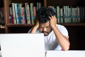 Der Mitarbeiter sitzt gestresst mit seiner Arbeit