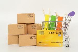Papierboxen und Einkaufstaschen in einem Wagen auf weißem Hintergrund. Online-Shopping- oder E-Commerce-Konzept und Lieferservice-Konzept foto
