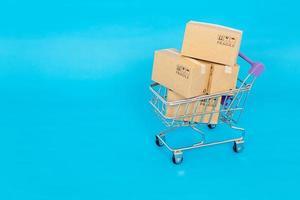 Papierkästen in einem Wagen auf einem blauen Hintergrund. Online-Shopping- oder E-Commerce-Konzept und Lieferservice-Konzept mit Kopierraum für Ihr Design