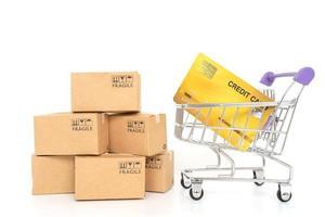 Papierboxen und eine Kreditkarte in einem Wagen auf einem weißen Hintergrund. Online-Shopping- oder E-Commerce-Konzept und Lieferservice-Konzept
