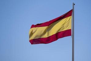 spanische Flagge auf einem Mast, der im Wind fliegt foto