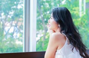 Porträt einer schönen asiatischen Frau, die glücklich am Fenster auf natürlichem Hintergrund sitzt
