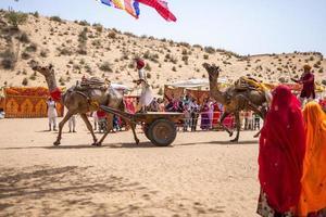 Rajasthan, Indien 2018 - Menschen, die mit Kamelen Kutschen durch die Wüste reiten