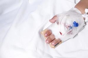 Babyhand mit Verband, der Kochsalzlösung auf Krankenhausbett gibt foto