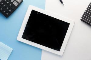 flache Zusammensetzung des digitalen Tabletts mit Bürolieferanten auf farbigem Hintergrund foto
