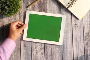 digitales Tablett mit grünem Bildschirm auf hölzernem Hintergrund