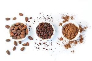 Kakaobohnensamen, Kakaonibs und Kakaopulver auf weißem Hintergrund foto