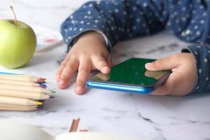 Kind Mädchen Cartoons auf Smartphone beobachten foto