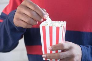 junger Mann, der Popcorn Nahaufnahme isst foto