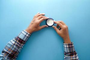 Behälter mit weißer Creme auf blauem Hintergrund foto