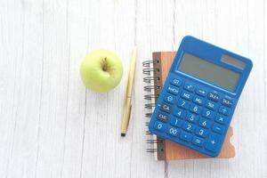 blauer Taschenrechner und Notizblock mit grünem Apfel
