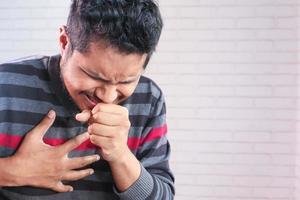 junger asiatischer Mann, der Nahaufnahme hustet und niest foto