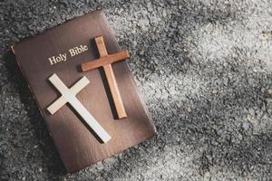 Nahaufnahme von einfachen hölzernen christlichen Kreuzen auf einer Bibel
