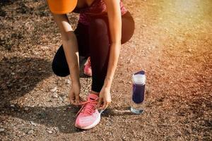 junge fitte Frau, die für Fitnesslauf im Park vorbereitet