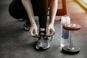Frau, die ihre Schnürsenkel bindet. Nahaufnahme des weiblichen Sport-Fitness-Läufers, der sich zum Joggen im Fitnessstudio fertig macht